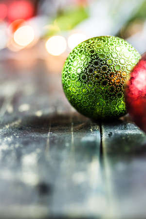 Traditional Christmas holiday ornaments on a dark stained wooden floor background.