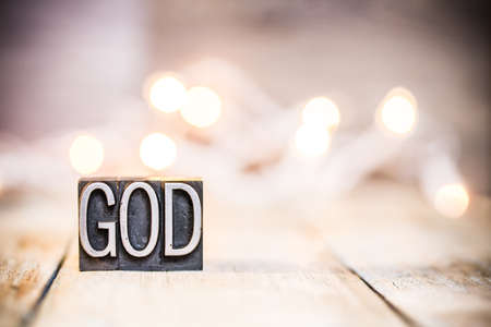 GOD written in vintage metal letterpress type on a bokeh light and wooden background. Stock Photo
