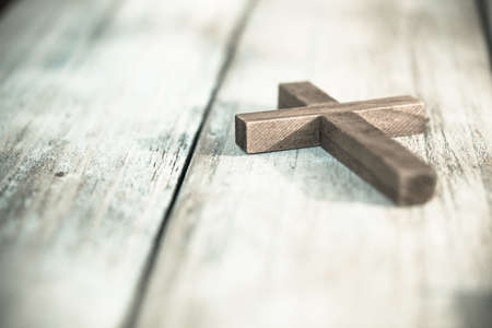A vintage wooden Christian cross crucifix on a wood plank background.