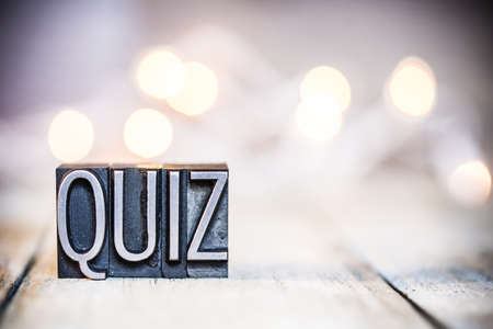 The word QUIZ written in vintage metal letterpress type on a bokeh light and wooden background.