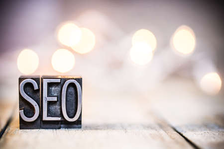 The word SEO written in vintage metal letterpress type on a bokeh light and wooden background.
