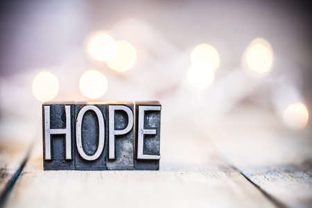 The word HOPE written in vintage metal letterpress type on a bokeh light and wooden background. Stock fotó