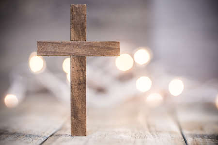 A wooden Christian cross on a soft bokeh light and wood background. Фото со стока