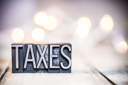 The word TAXES written in vintage metal letterpress type on a bokeh light and wooden background.