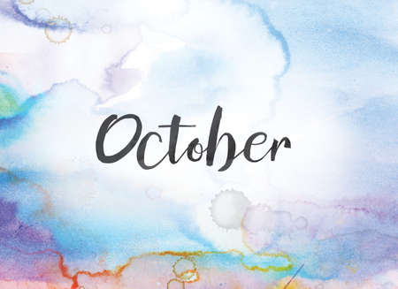 The word October concept and theme written in black ink on a colorful painted watercolor background. Stock Photo
