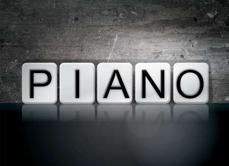 The word Piano concept and theme written in white tiles on a dark background. Banco de Imagens