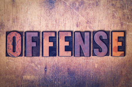 The word Offense concept and theme written in vintage wooden letterpress type on a grunge background. Imagens
