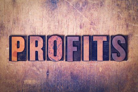 The word Profits concept and theme written in vintage wooden letterpress type on a grunge background.
