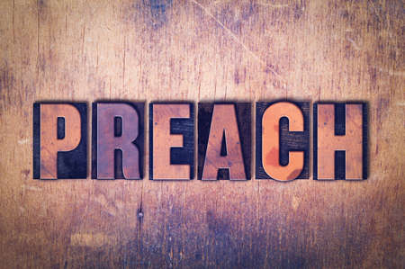 The word Preach concept and theme written in vintage wooden letterpress type on a grunge background.