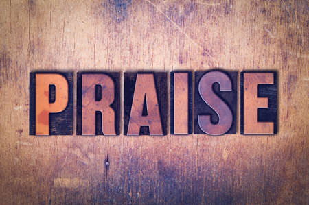 The word Praise concept and theme written in vintage wooden letterpress type on a grunge background. Stock Photo