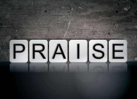 The word Praise concept and theme written in white tiles on a dark background.