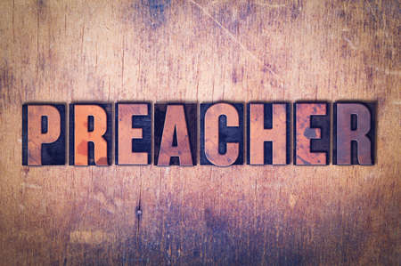 The word Preacher concept and theme written in vintage wooden letterpress type on a grunge background. Stock Photo