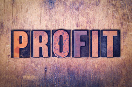 The word Profit concept and theme written in vintage wooden letterpress type on a grunge background.