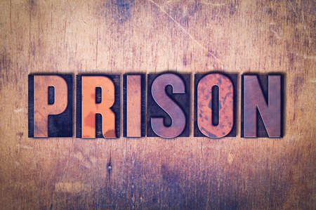 The word Prison concept and theme written in vintage wooden letterpress type on a grunge background. Фото со стока
