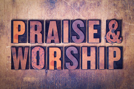 The words Praise  & Worship concept and theme written in vintage wooden letterpress type on a grunge background.