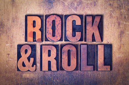 The words Rock and  Roll concept and theme written in vintage wooden letterpress type on a grunge background.