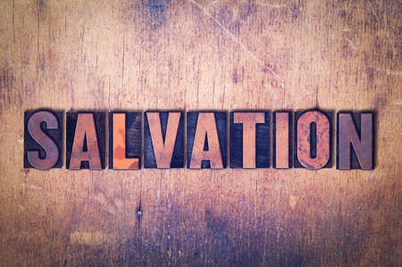 The word Salvation concept and theme written in vintage wooden letterpress type on a grunge background.