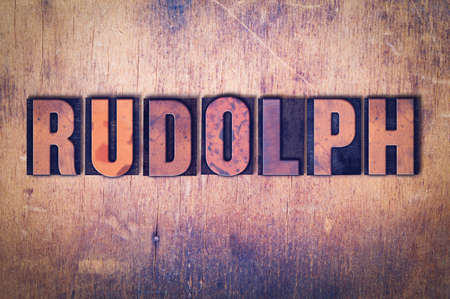 The word Rudolph concept and theme written in vintage wooden letterpress type on a grunge background.