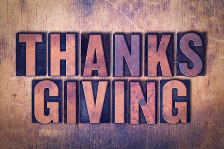 The word Thanksgiving concept and theme written in vintage wooden letterpress type on a grunge background.