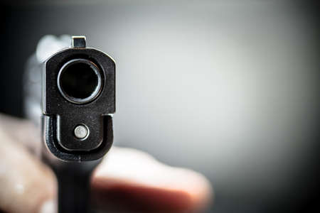 A person aiming and pulling the trigger of a pistol hand gun with background. Stock Photo