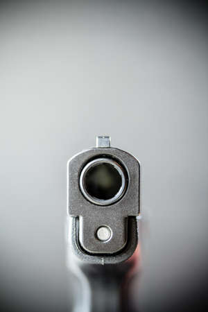 A black pistol hand gun pointed at the viewer.
