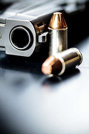 A black pistol hand gun with bullets. Stock Photo