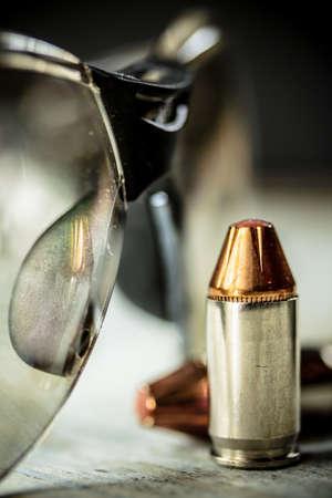 弾丸と安全射撃メガネを持つ黒いピストルハンドガン。 写真素材 - 92737624