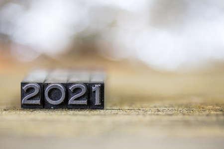 Das Konzept des Jahres 2021 geschrieben in Weinlese Retro- Metallbriefbeschwererart auf einen hölzernen Hintergrund.