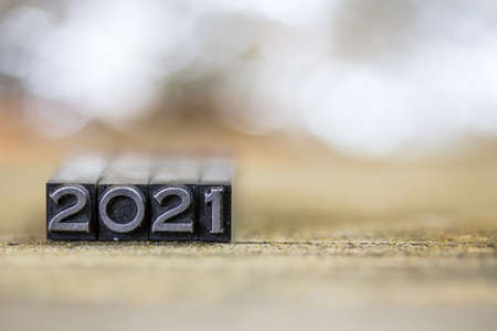 The year 2021 concept written in vintage retro metal letterpress type on a wooden background. 版權商用圖片