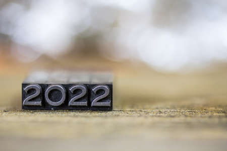 The year 2022 concept written in vintage retro metal letterpress type on a wooden background. Stock Photo