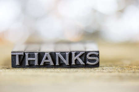 The word THANKS concept written in vintage retro metal letterpress type on a wooden background.