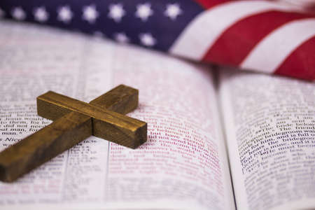 A holy Christian cross laying on an open Bible with an American flag in the background.