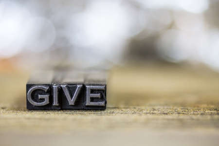 The word GIVE concept written in vintage retro metal letterpress type on a wooden background.