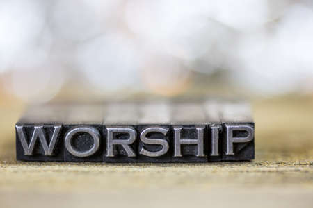 The word WORSHIP concept written in vintage retro metal letterpress type on a wooden background.