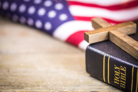 A wooden Christian cross laying on a holy Bible with an American flag background. Banque d'images