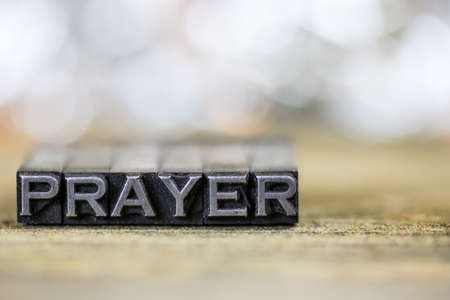 The word PRAYER concept written in vintage retro metal letterpress type on a wooden background.