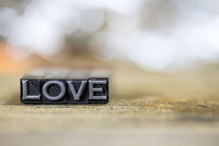 The word LOVE concept written in vintage retro metal letterpress type on a wooden background.