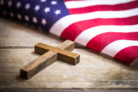 Ein heiliges hölzernes christliches Kreuz , das auf einem hölzernen Hintergrund mit einer Staatsflagge legt