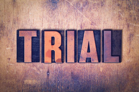The word Trial concept and theme written in vintage wooden letterpress type on a grunge background.