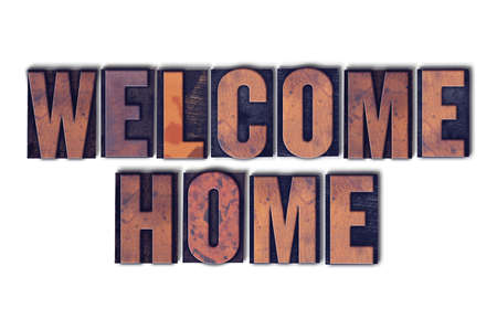 The words Welcome Home concept and theme written in vintage wooden letterpress type on a white background. Stock Photo