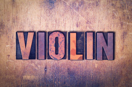 The word Violin concept and theme written in vintage wooden letterpress type on a grunge background.