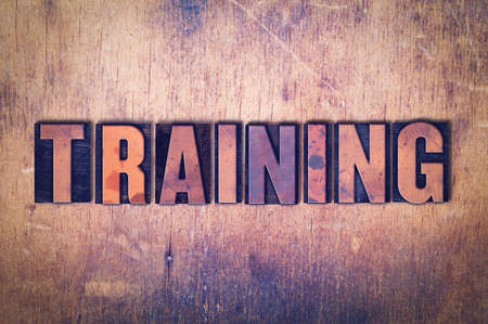 The word Training concept and theme written in vintage wooden letterpress type on a grunge background. Imagens