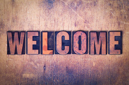 The word Welcome concept and theme written in vintage wooden letterpress type on a grunge background.