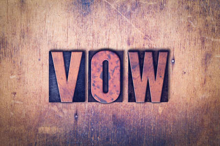 The word Vow concept and theme written in vintage wooden letterpress type on a grunge background.