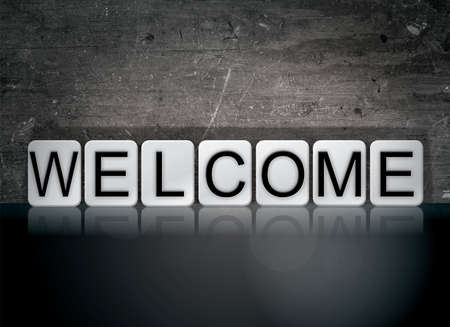 The word Welcome concept and theme written in white tiles on a dark background. Banco de Imagens
