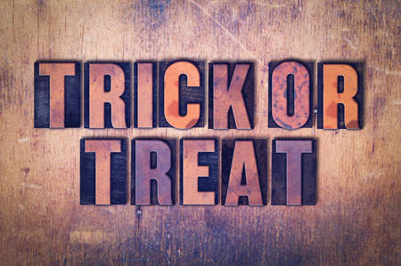 The words Trick or Treat concept and theme written in vintage wooden letterpress type on a grunge background. Фото со стока