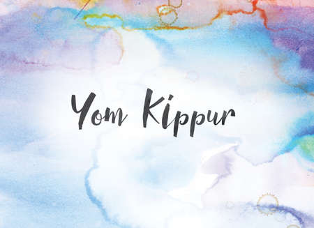 The words Yom Kippur concept and theme written in black ink on a colorful painted watercolor background.