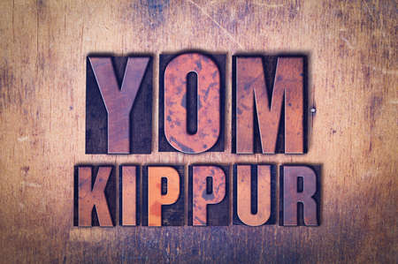 The words Yom Kippur concept and theme written in vintage wooden letterpress type on a grunge background.