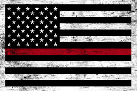 A firefighter support flag stained over a weathered white wooden background.