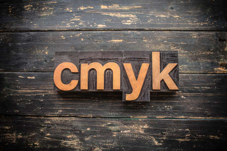 """The word """"CMYK"""" written in vintage wood letterpress type on a vintage rustic background. Stock Photo"""